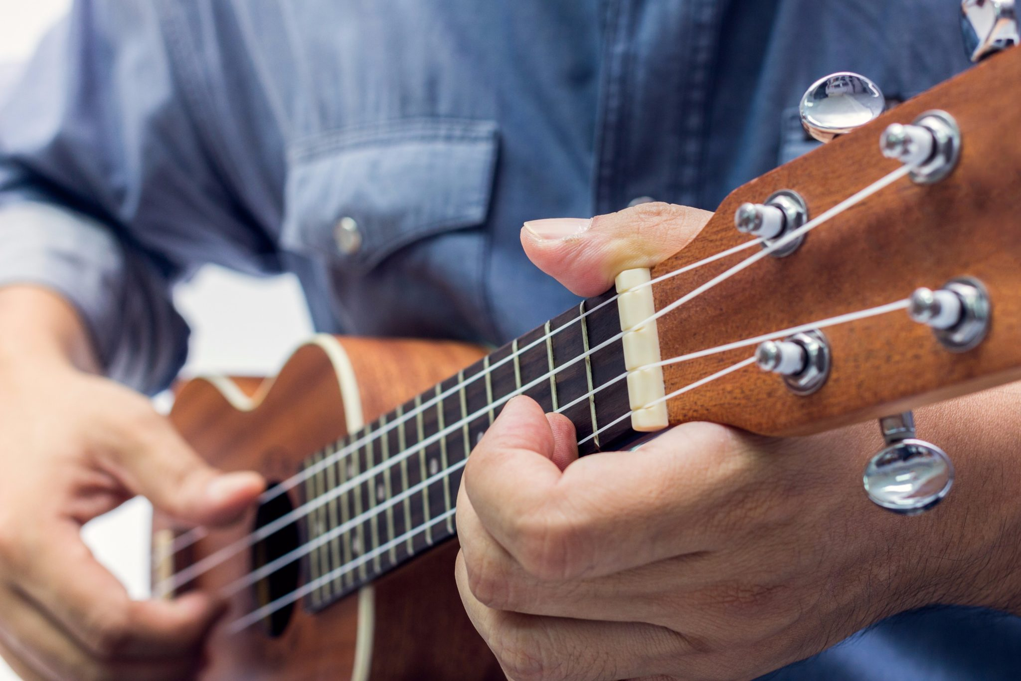 The man playing a brown ukulele